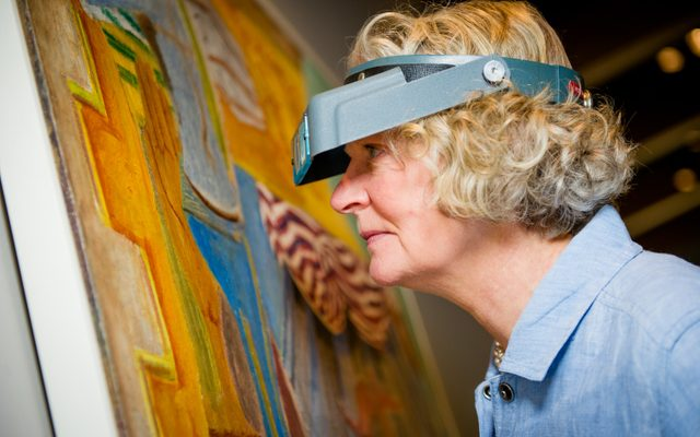 Conservator Gay Myers inspects an artwork in the gallery
