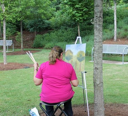 Person sitting outside on a folding stool holding paint brushes while painting on a canvas