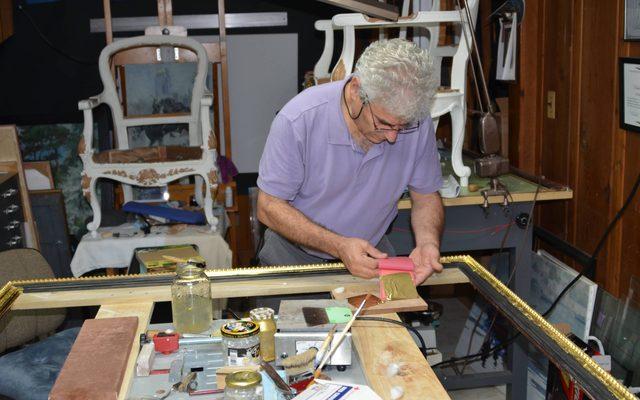 Conservator working on frame for artwork