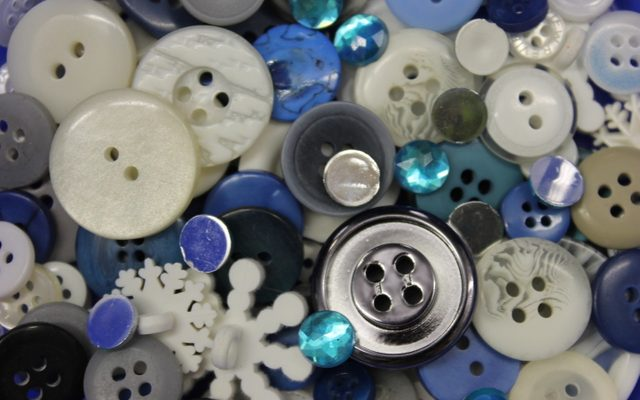 Circle shaped buttons in white, blues, and grays and some snowflake shaped white buttons
