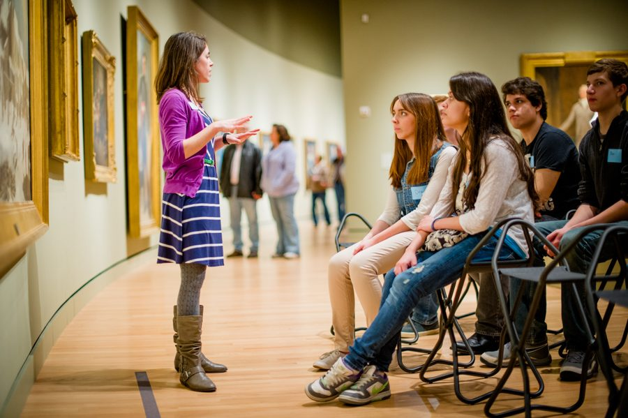 Woman stands in front of group of guests giving tour of art