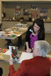 Educator Amanda Driver and a participant look at a collage in progress.