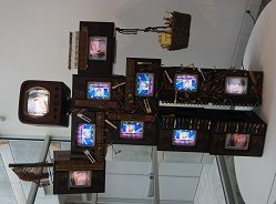 Nam June Paik (South Korean, 1932 – 2006) John Cage Robot II, 1995 11 vintage wood TV cabinets, 10 Panasonic color television receivers, 1 Samsung color television receiver, 2 DVD players, and 2 channels of original Paik software on DVDs. Mixed media elements including piano keys and piano hammers, piano wire, acrylic paint, basket, books, wood mushrooms, chessmen 108 x 80 x 31 in. (274.3 x 203.2 x 78.7 cm)