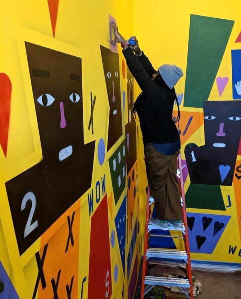 African American artist Nina Chanel Abney stands on a ladder and reaches up to spray paint into a stencil she holds against the wall. She is surrounded by a large colorful mural of faces, symbols and shapes.