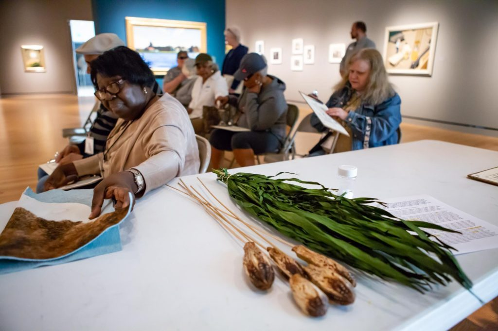 """A woman from the Arkansas Council of the Blind picks up multisensory tour materials representing Yasuo Kuniyoshi's painting entitled """"Little Joe with Cow"""" from a table."""