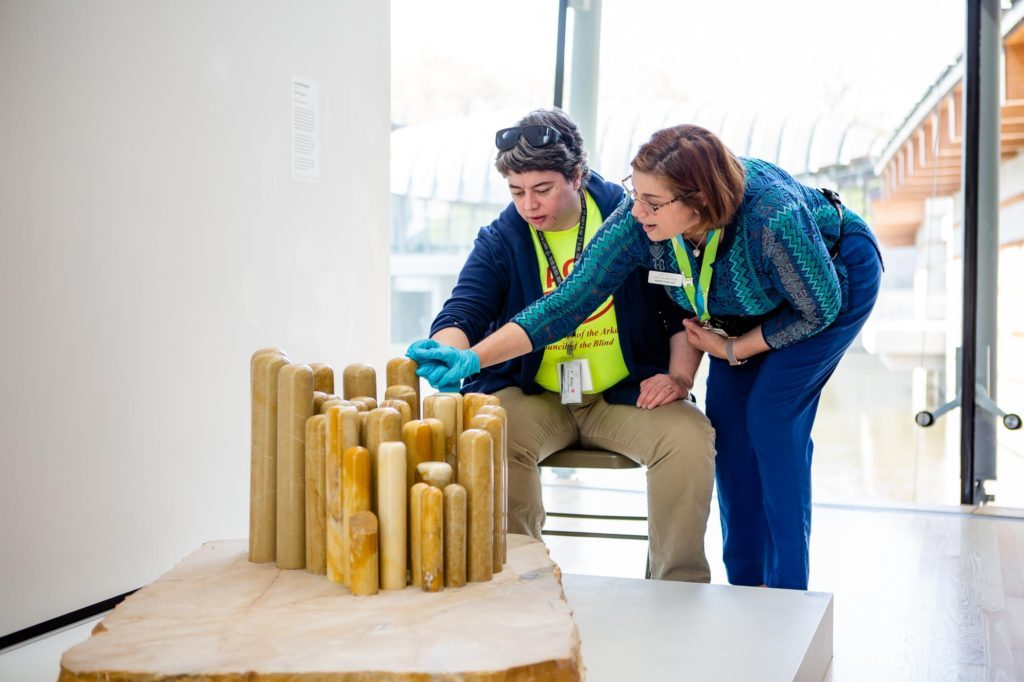 """A museum educator and a participant wear blue nitrile gloves as the educator guides the participant's hand over Louise Bourgeois' marble sculpture entitled """"Distant Figures."""""""