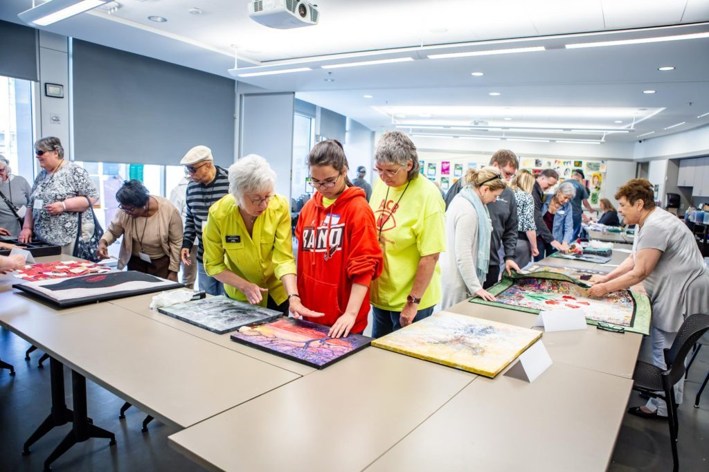 Museum staff and volunteer artists describe their artworks and artistic processes as the participants feel their artworks.