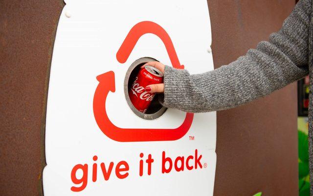 Hand throwing coke can in a recycling bin