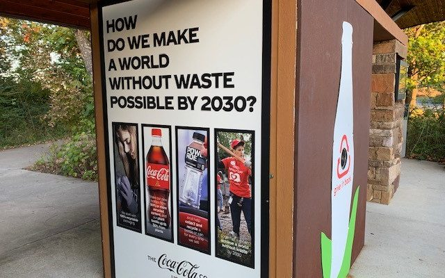 Photo of recycling bin with poster asking how to reduce waste