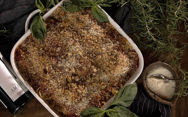 Casserole in baking dish surrounded by fresh herbs