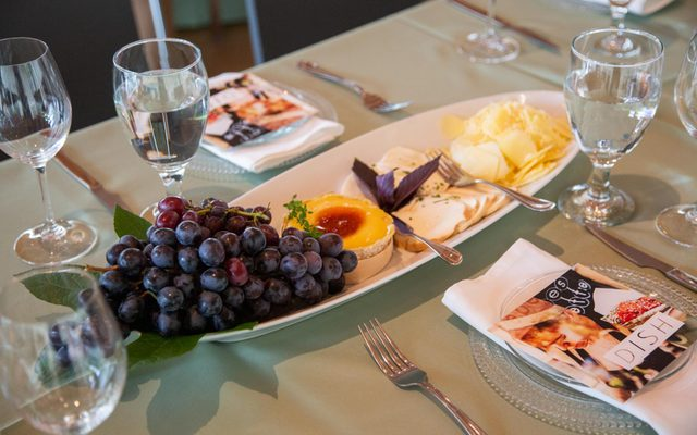 large plate with fresh fruit and cheese surrounded by place settings with water
