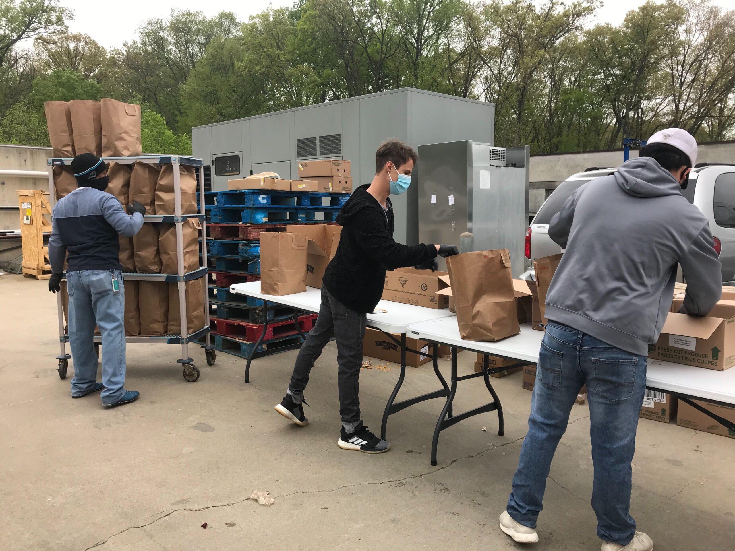 Staff members pack meals for school children at Crystal Bridges.