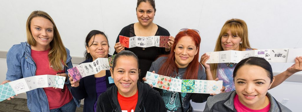 Adult English language learners from the Springdale Family Literacy Program stand and smile while showcasing flipbooks with pictures and words they created as part of the program.