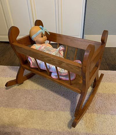 Baby doll in wooden crib