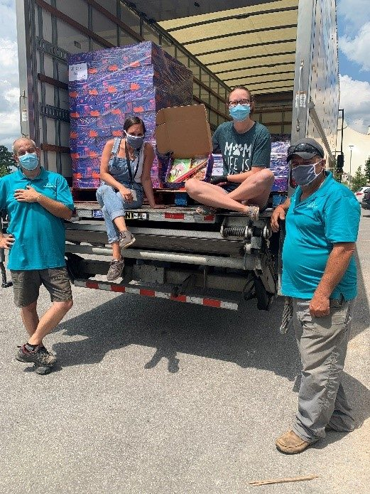 Group of people loading art kits into delivery truck