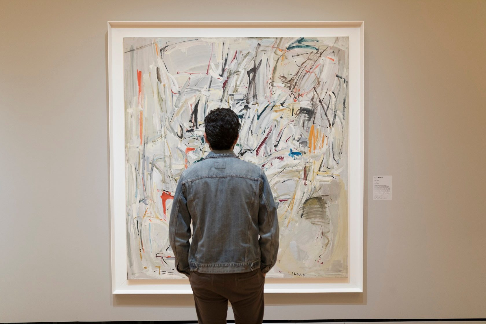 Man stands looking at abstract painting in front of him