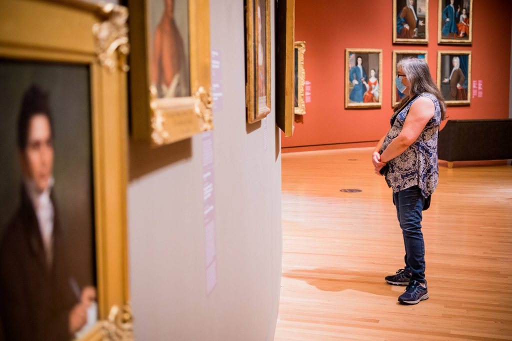 woman in a health mask stands looking at artwork