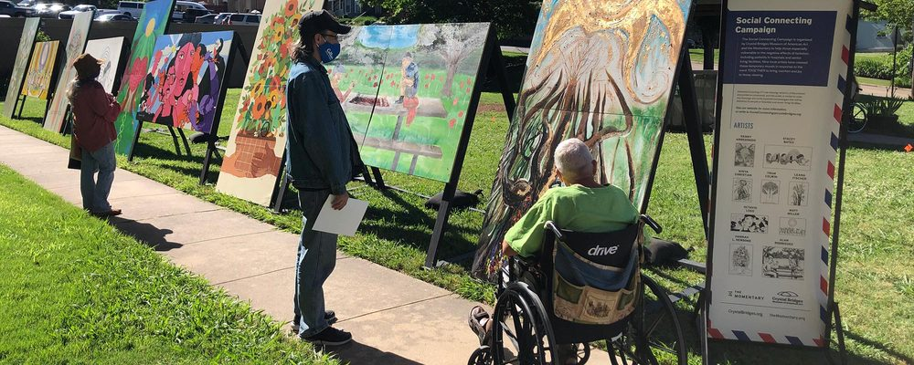 people viewing art at an outdoor community art show