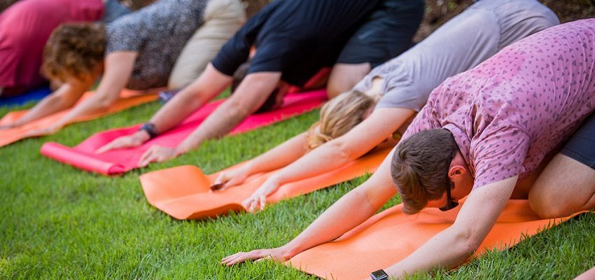 group of people doing yoga on mats outside