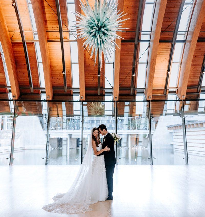 Bride and groom embracing beneath hanging glass sculpture