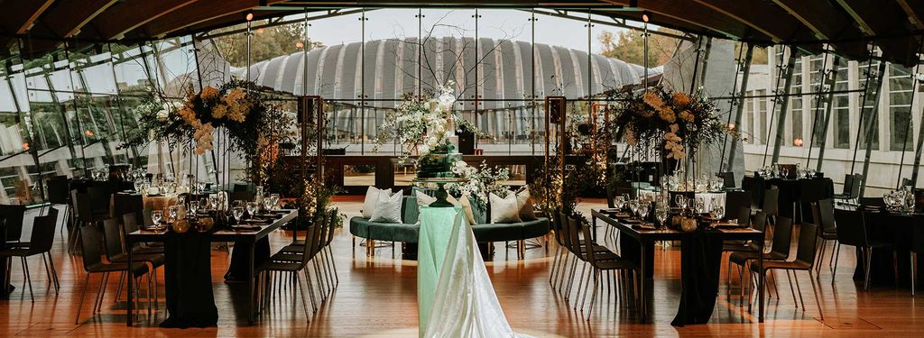 Great Hall set up with dinning tables and chairs and floral arrangements