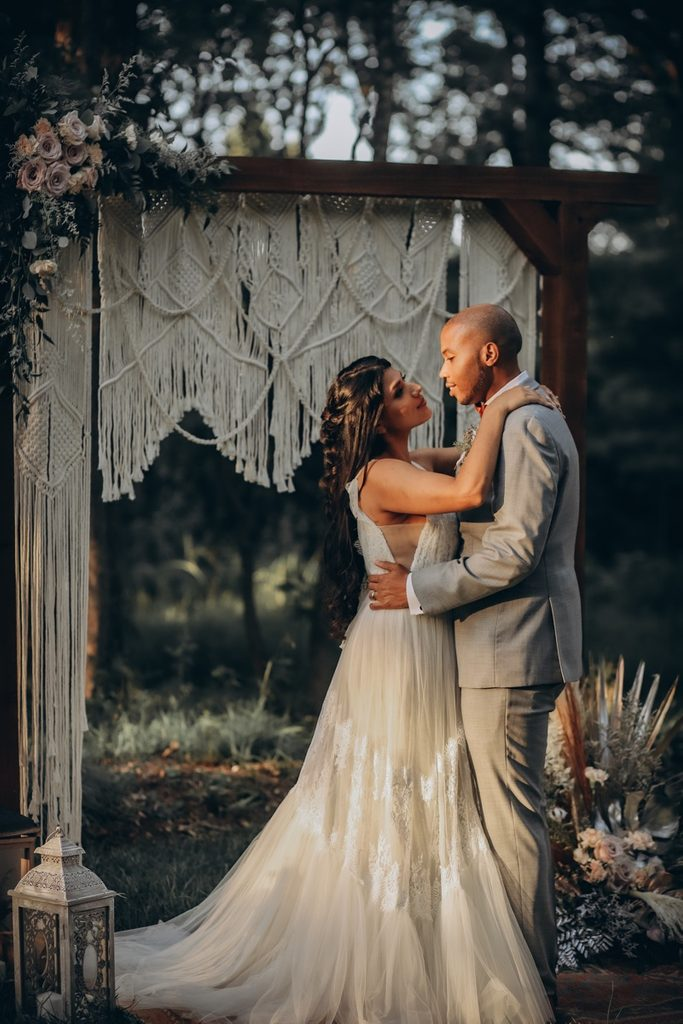 Bride and groom embrace while looking at each other under archway