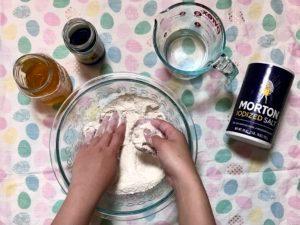 Hands mixing salt dough ingredients