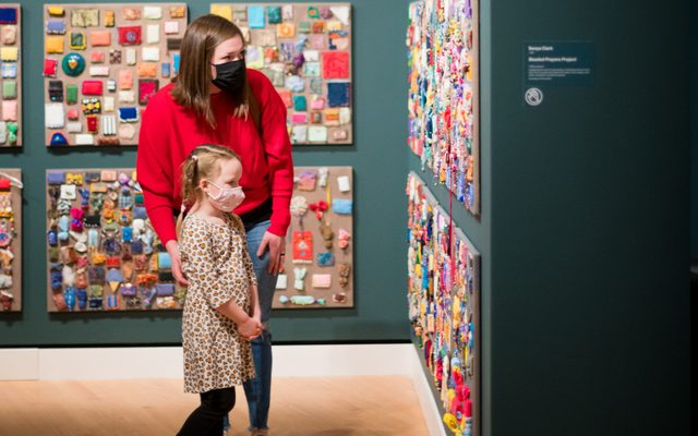 Woman and little girl, masked, looking at artwork hanging on the wall
