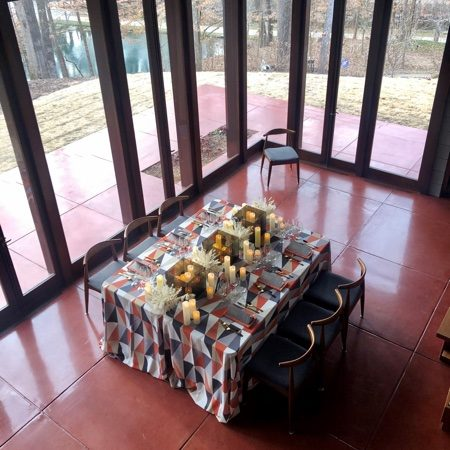 Table covered with table cloth and set with candles and flowers