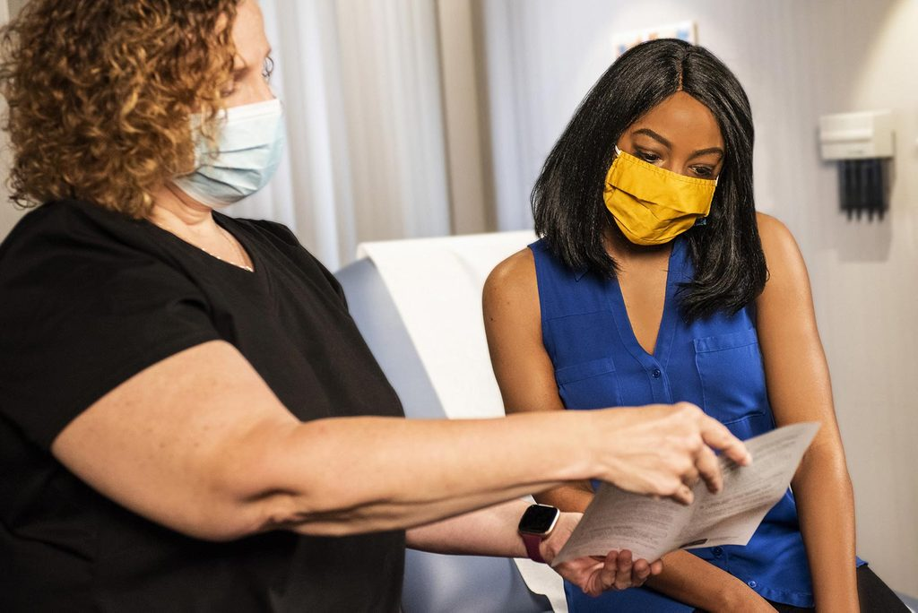 Two people wearing masks looking at medical documents