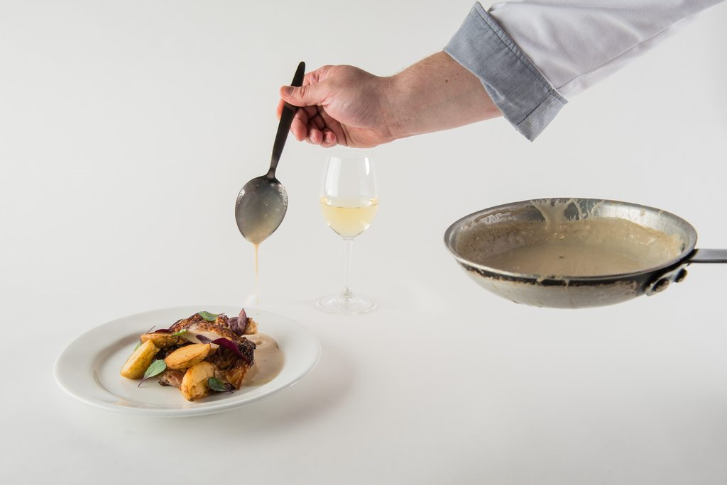 Chef's arm coming into frame from a pan to pour sauce from a spoon onto a plate of food
